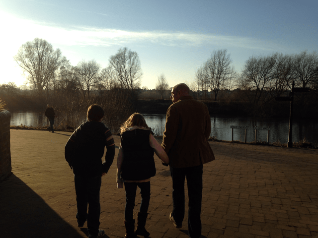 Hebe, her dad and brother, walking next to a river at sunset