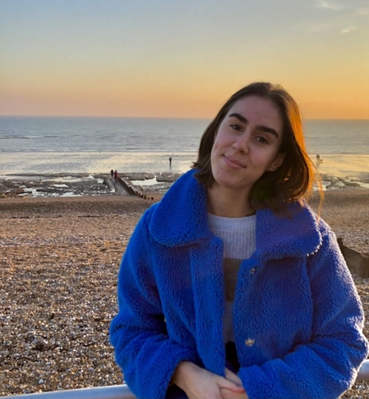 Teigan aged 18 wearing a blue coat and smiling with a beach in the background