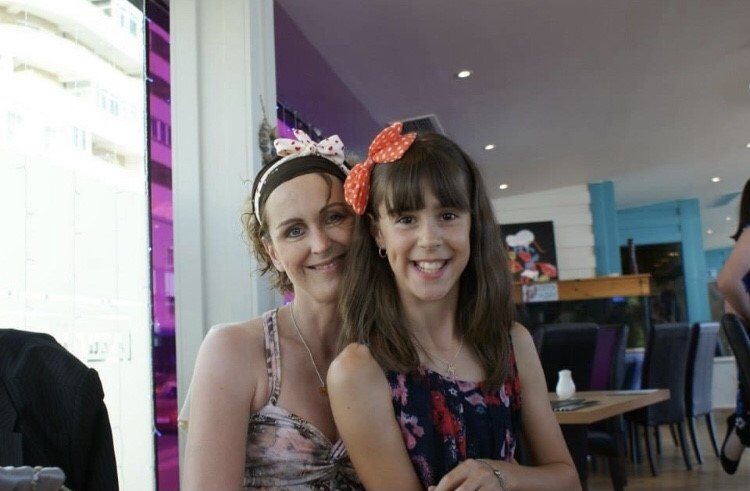 Teigan as a young girl sat on her mum's lap, both smiling